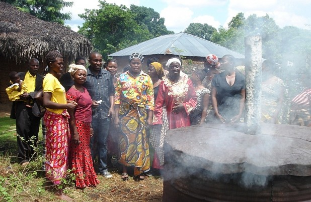 Villagers monitoring the progress of their charcoal kiln