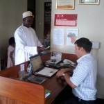 Mr. Rashidi Saidi Mpute, making payment on the Tumani groups new electrical briquette extruder