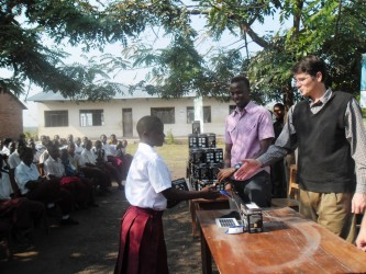 Nick Stubbs from Transmar Tanzania congratulates a student from Makwale Secondary School, who has just received a solar lantern